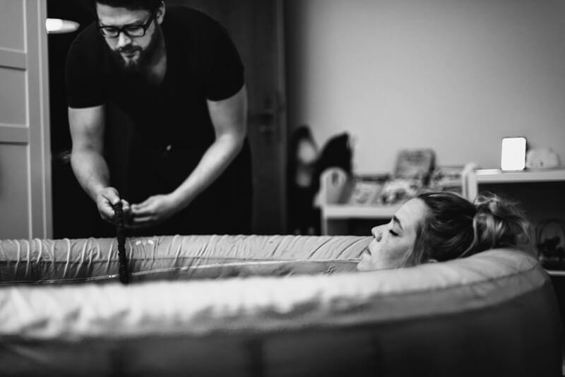 Frau liegt während der Wehen im Geburtspool, Mann checkt Schlauch