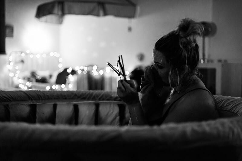 Frau schminkt sich im Geburtspool ab, Geburtsfotografie