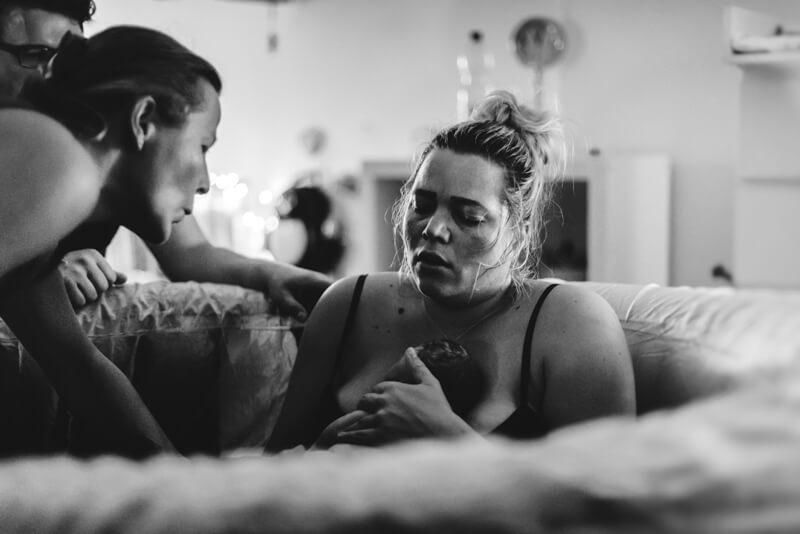 Frau kurz nach der Entbindung ihres Neugeborenen im Geburtspool, Geburtsfotografie